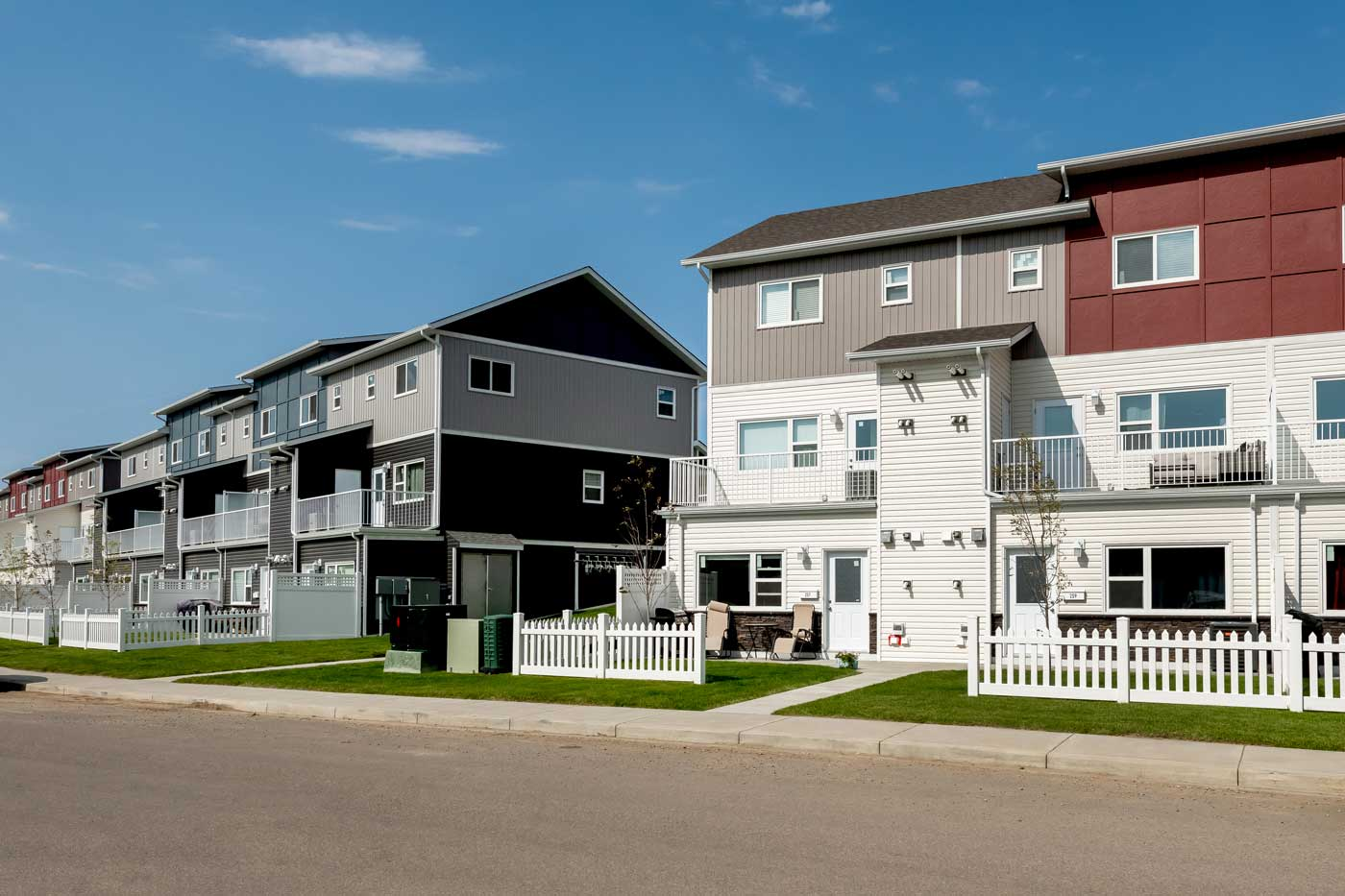 Cory Villas townhouses in Saskatoon, Sask. Some of the siding is red, white and grey while the building next to it is blue, grey, and black.
