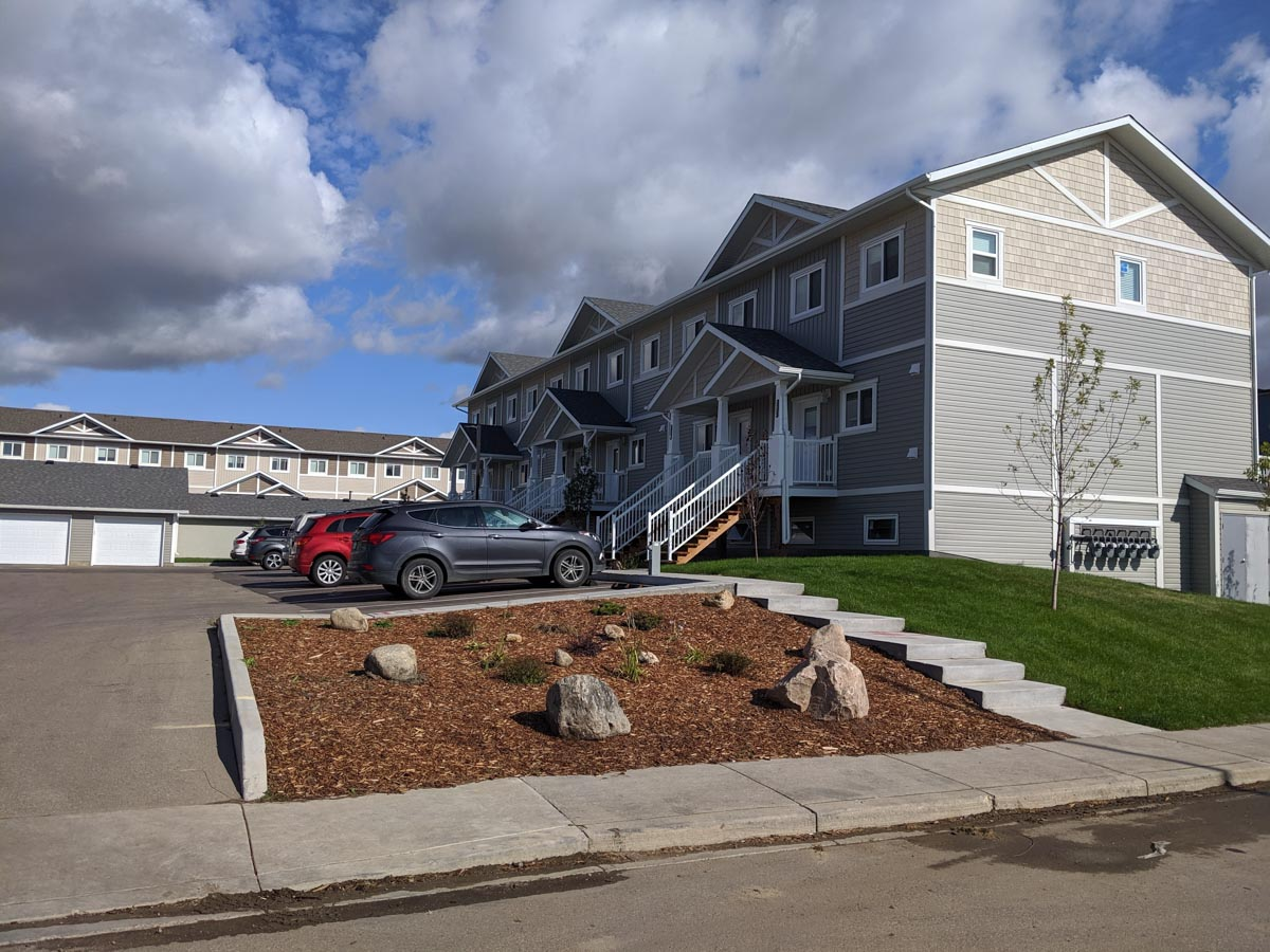 Urban Flats 2 townhouses in Saskatoon, Sask. The siding is grey and white. The photo shows the garage to the left.