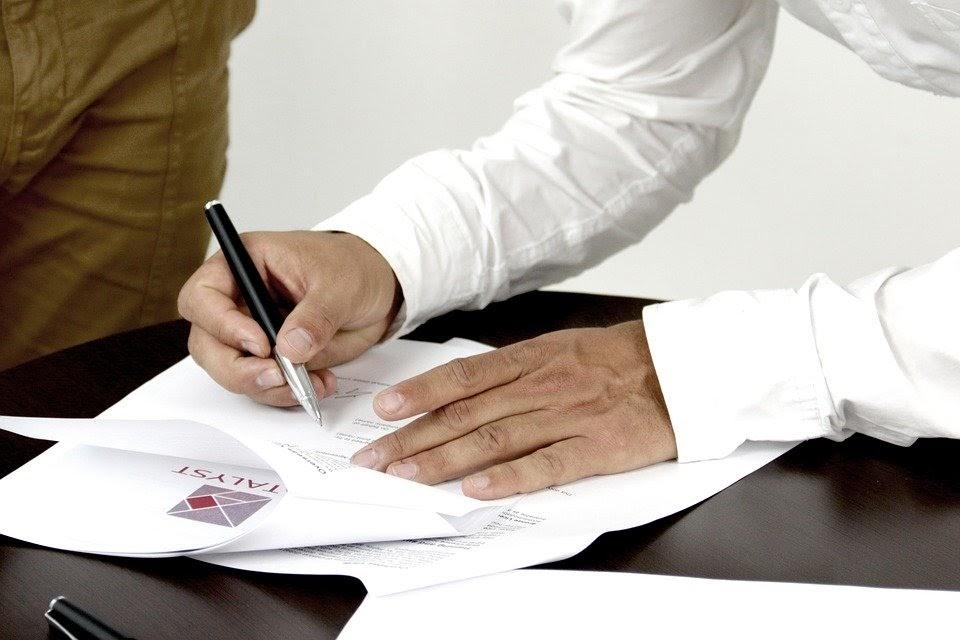 Muž podepisující smlouvu.