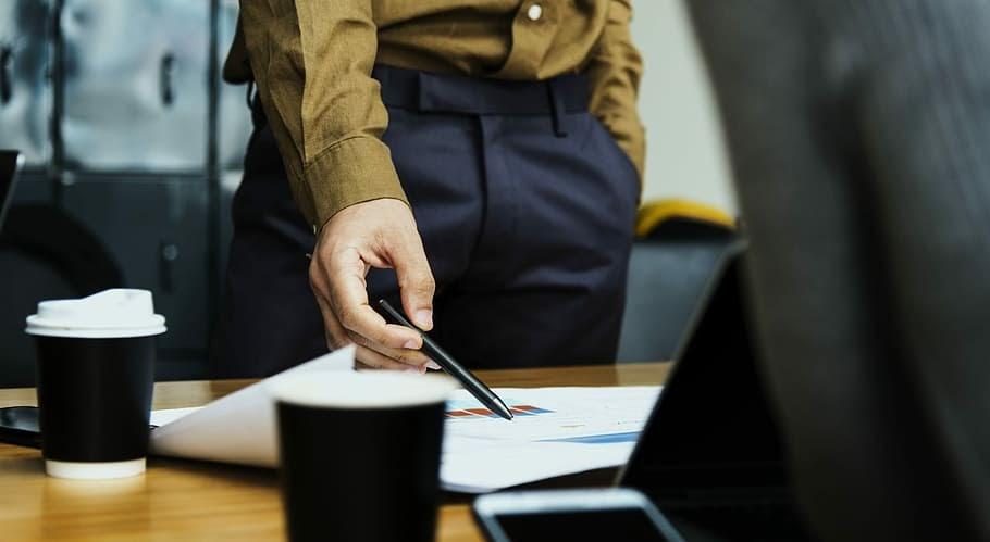 Muž ukazující na grafy v dokumentech.