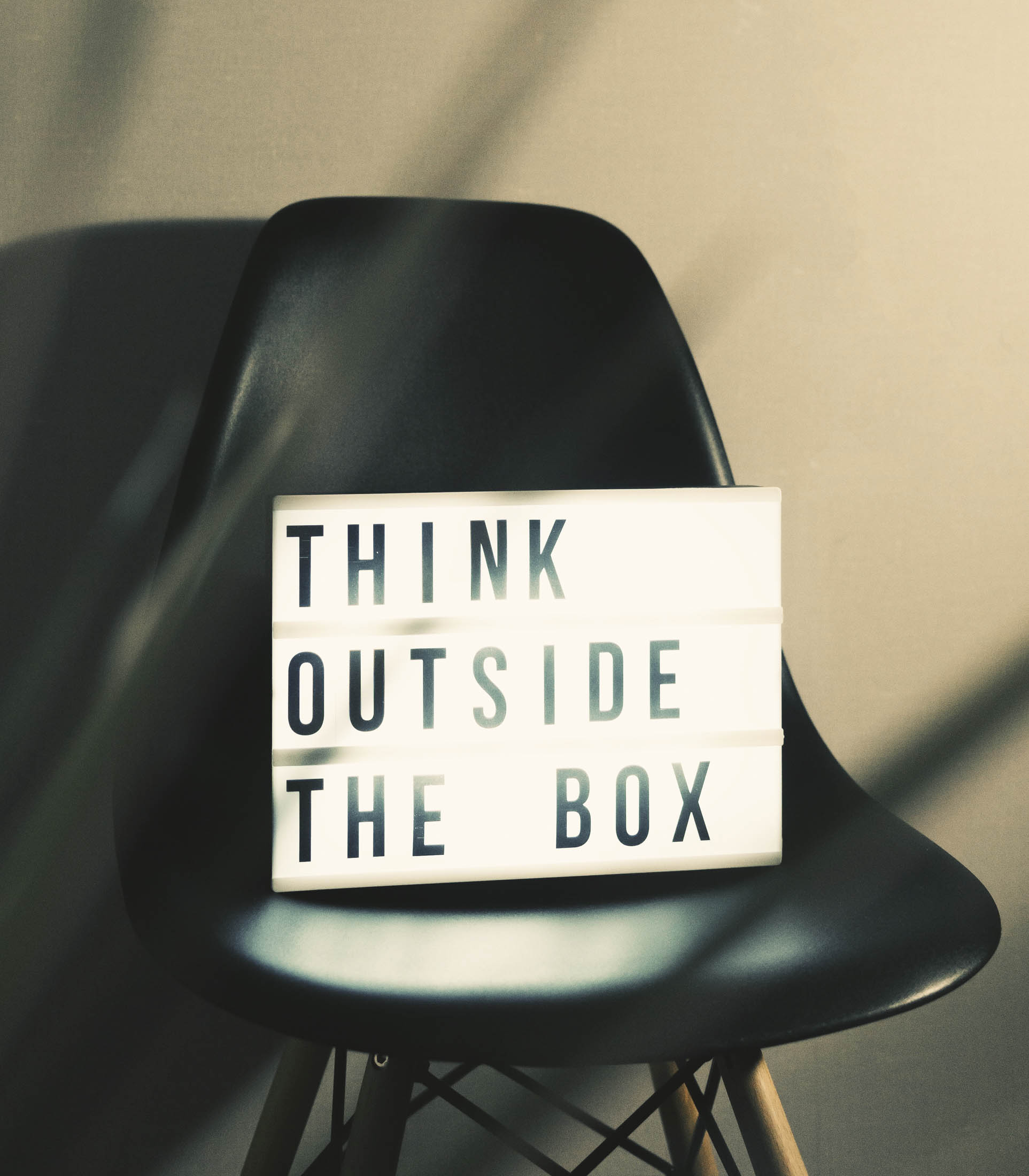 A sign with the words Think Outside the Box
