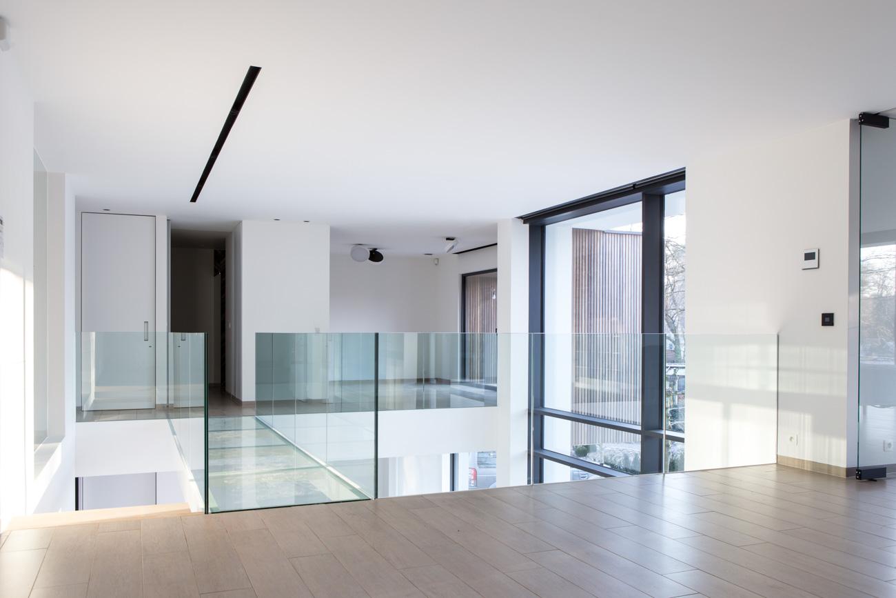 Woning Waasmunster minimalistisch interieur verdieping hal vide met glazen brug