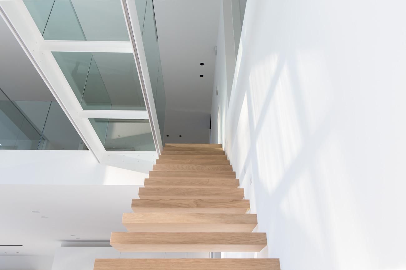 Woning Waasmunster minimalistisch interieur houten zwevende trap vide met glazen brug