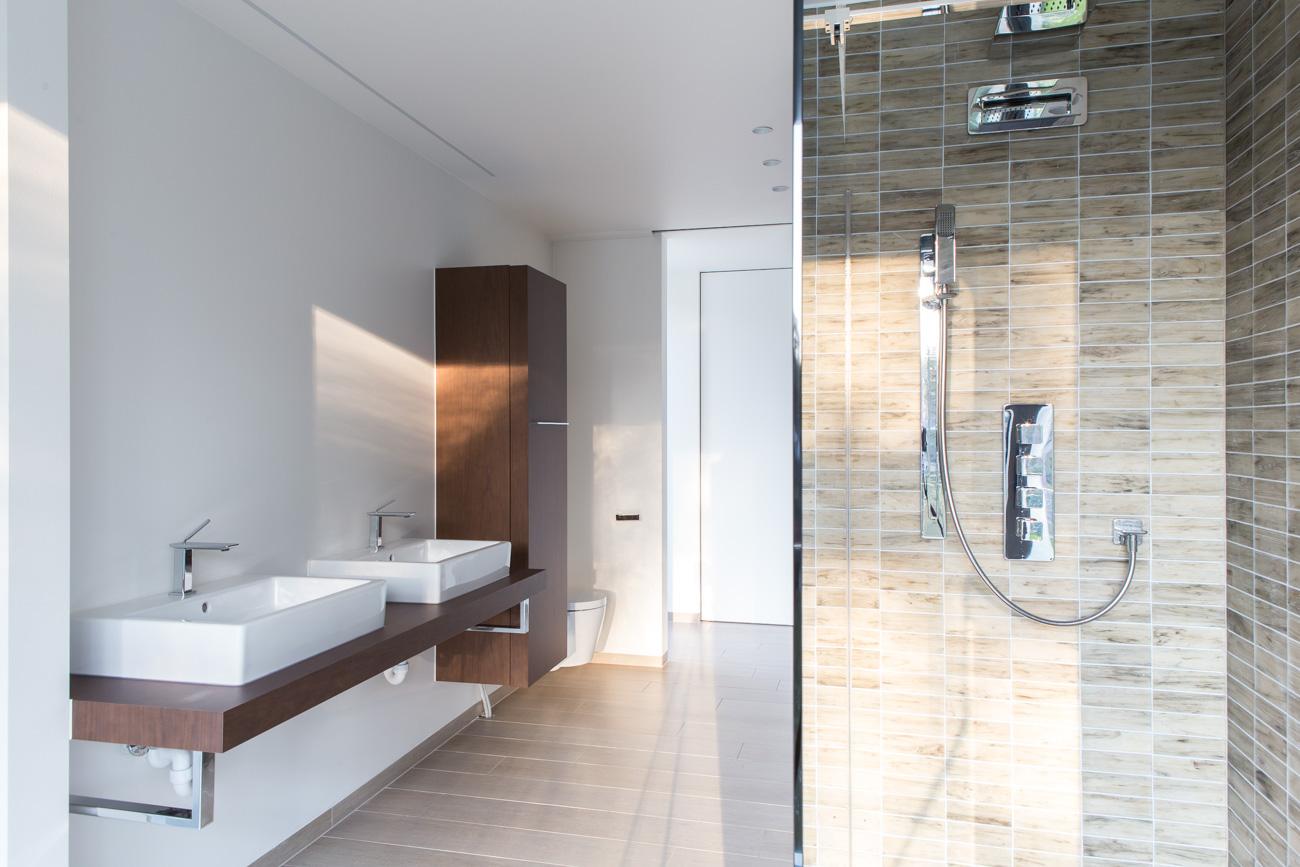 Woning Waasmunster minimalistisch interieur badkamer met houten lavabomeubel