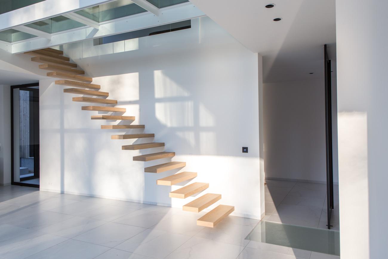 Woning Waasmunster minimalistisch interieur traphal met houten zwevende trap