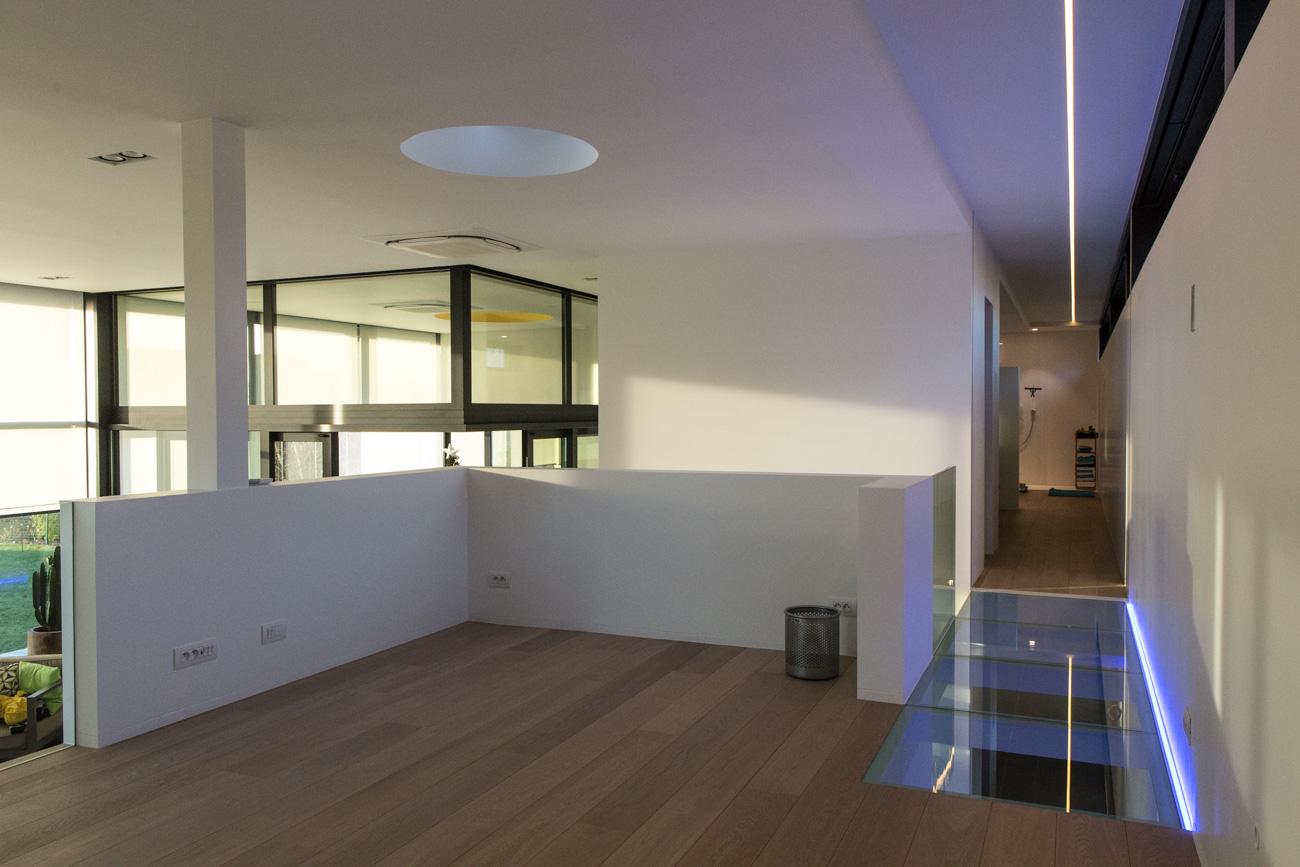 Woning in Sint-Amandsberg minimalistisch interieur verdipeing hal met neon licht _glazen brug