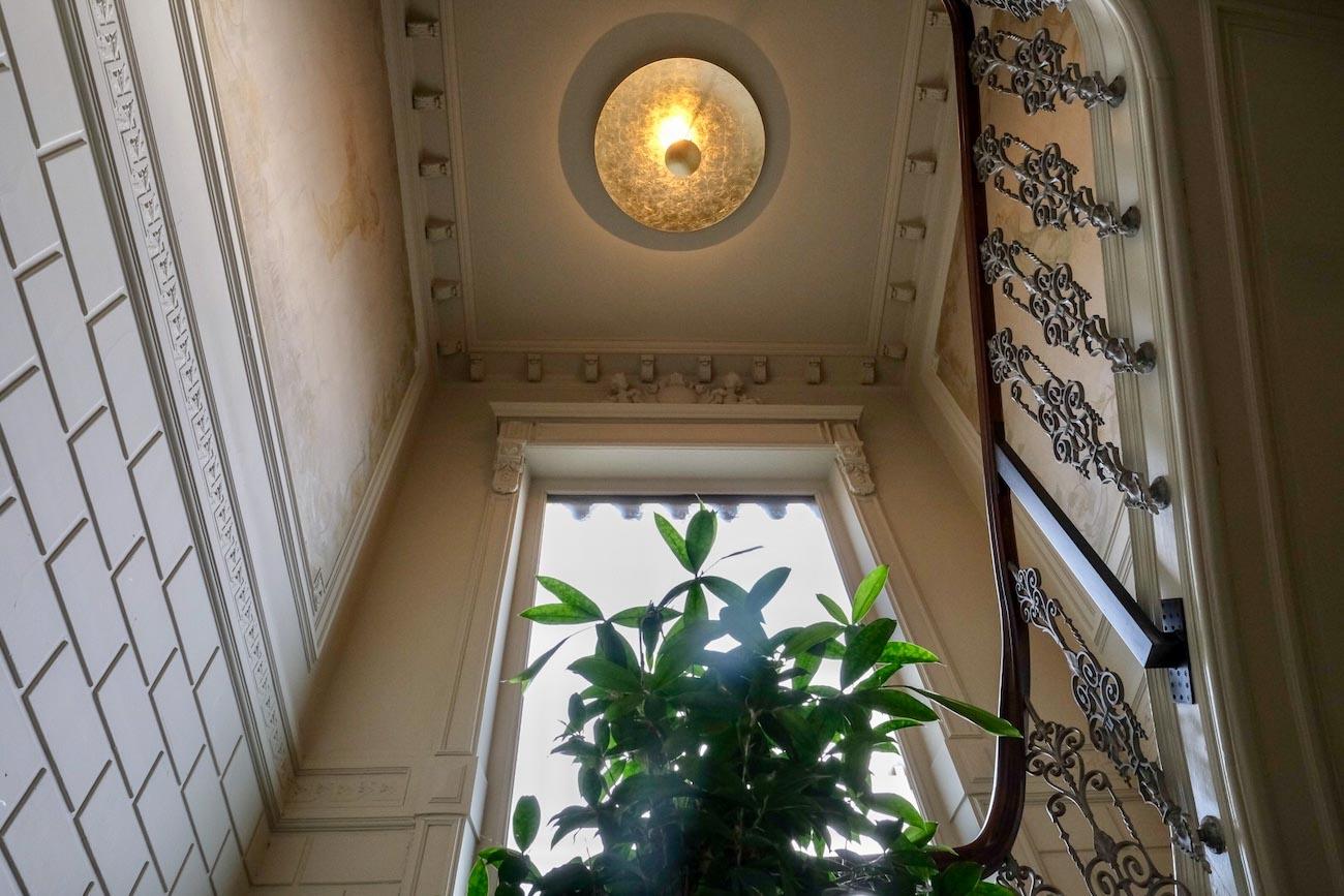 The Mansion Hotel Gent Vide en houten trap met opengewerkte ijzeren leuning erfgoed restoratie