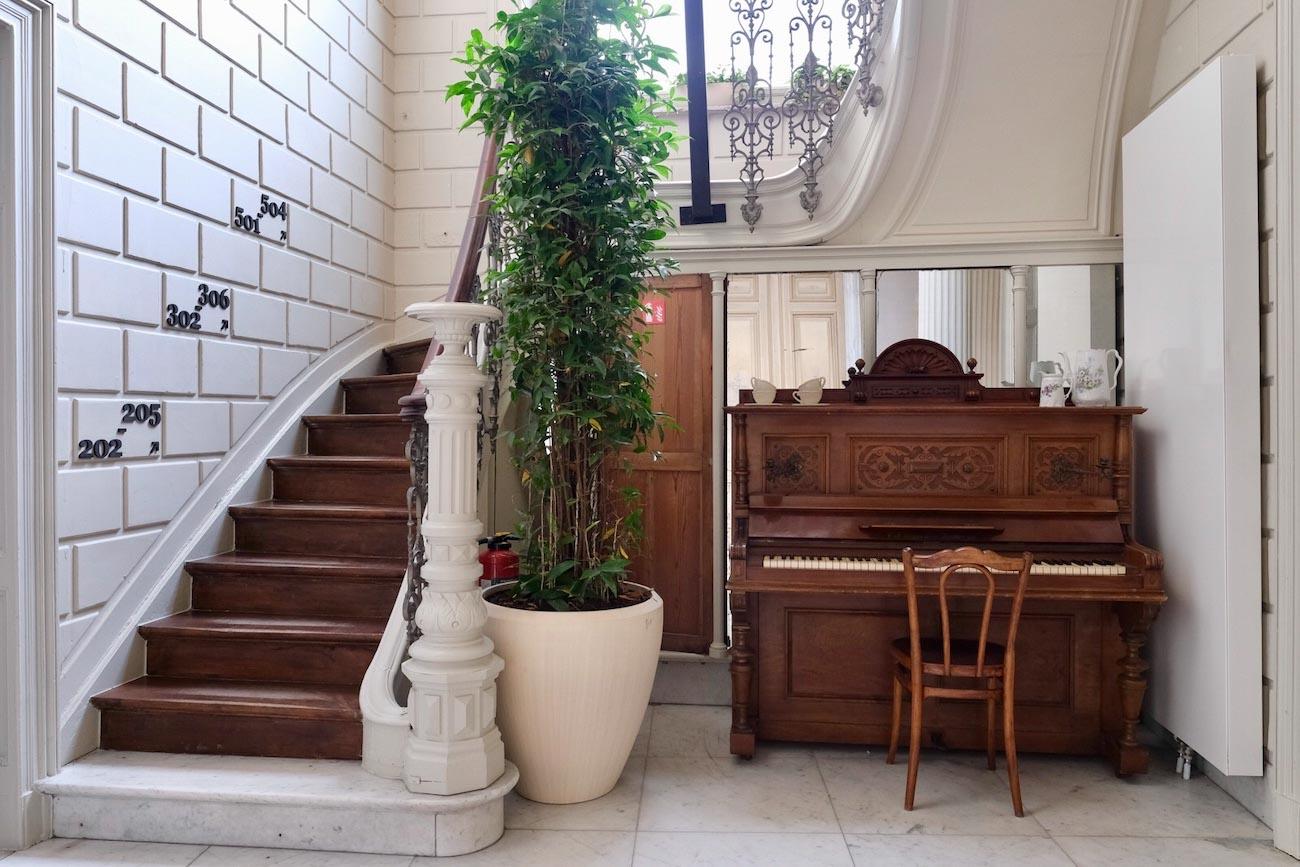 The Mansion Hotel Gent Traphal houten trap met opengewerkte ijzeren leuning erfgoed restoratie