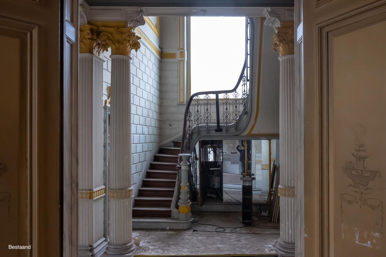 The Mansion Hotel Gent Traphal houten trap met opengewerkte ijzeren leuning bestaand
