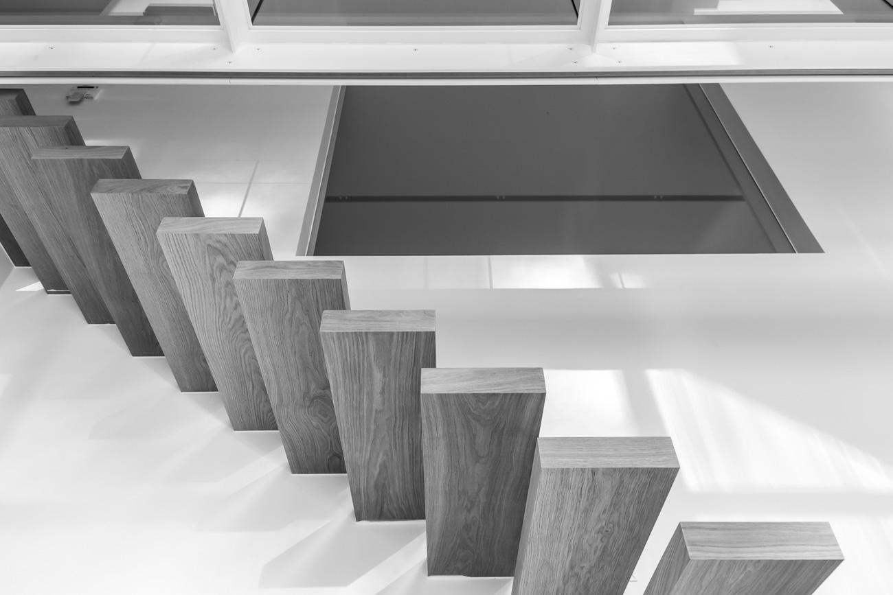 Woning Waasmunster minimalistisch interieur traphal met houten zwevende trap zwart wit
