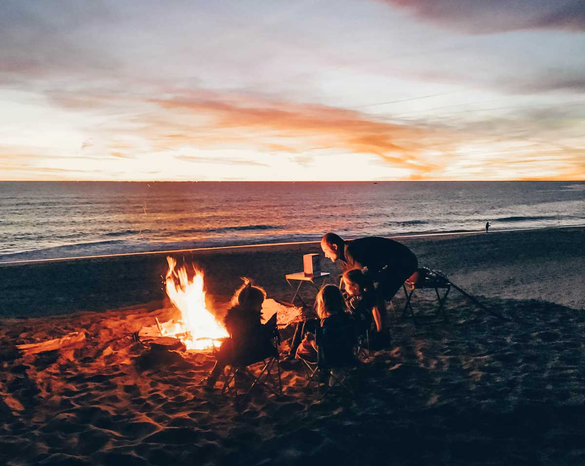 Family sitting around a fire on the beach