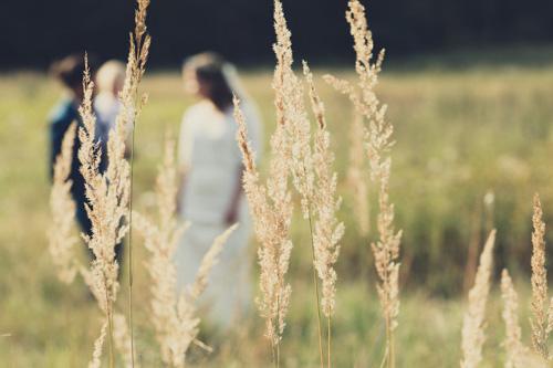 Wedding Photography Projekt. Junges Brautpaar mit kleinem Kind auf einer großen Wiese.