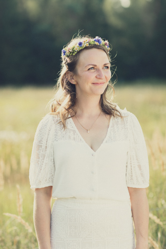 Hochzeitsfotografie Projekt. Junge Frau in weißem Hochzeitskleid vor einer großen Wiese.