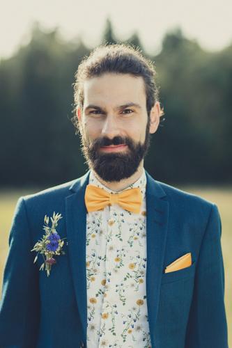 Hochzeitsfoto Projekt. Junger Bräutigam in dunkelblauem Anzug vor einer großen Wiese und Wald.