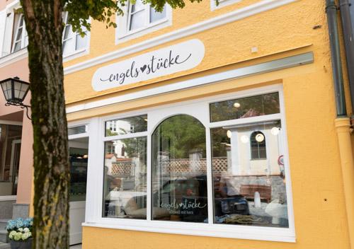 Corporate Design Projekt. Einzigartiges Logo Design an der leuchtend gelben Fassade des Concept Stores engelsstücke in Murnau am Staffelsee.