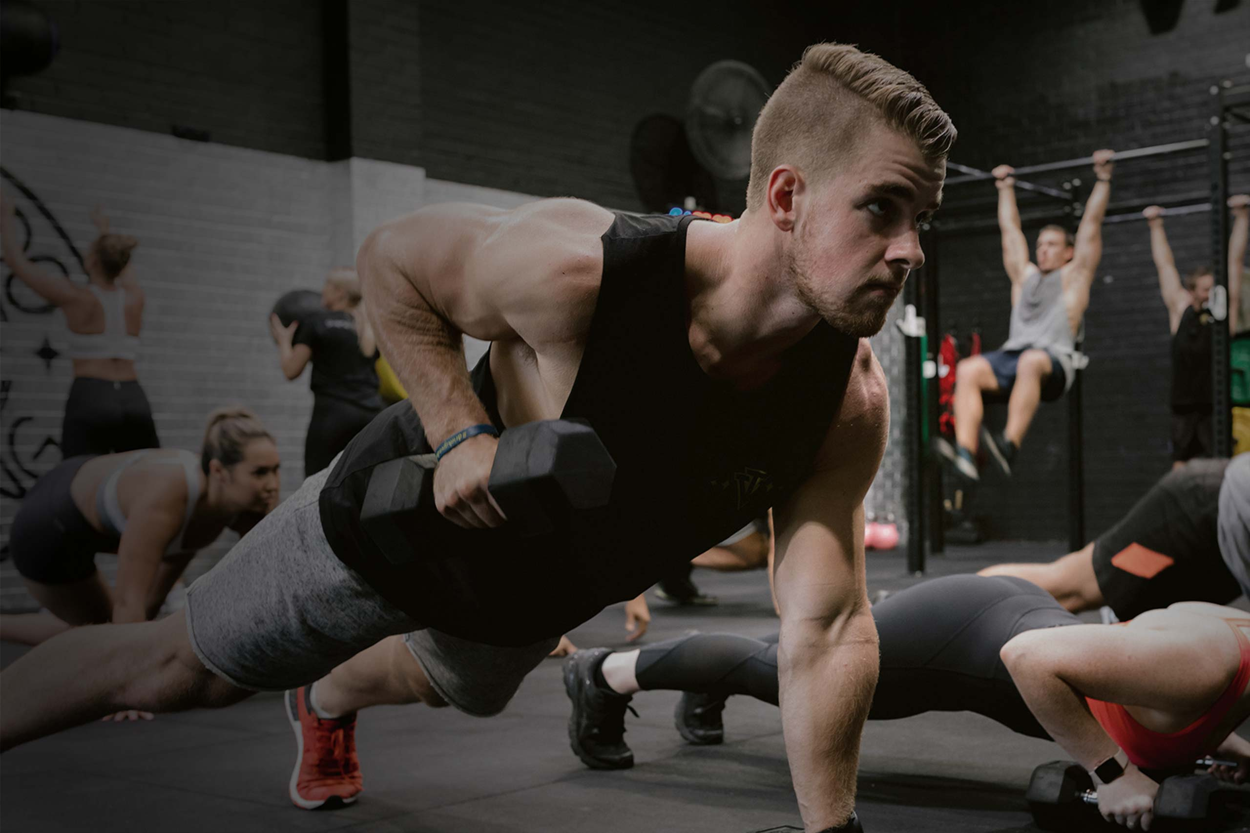 male athlete lifting dumbbells in group training class