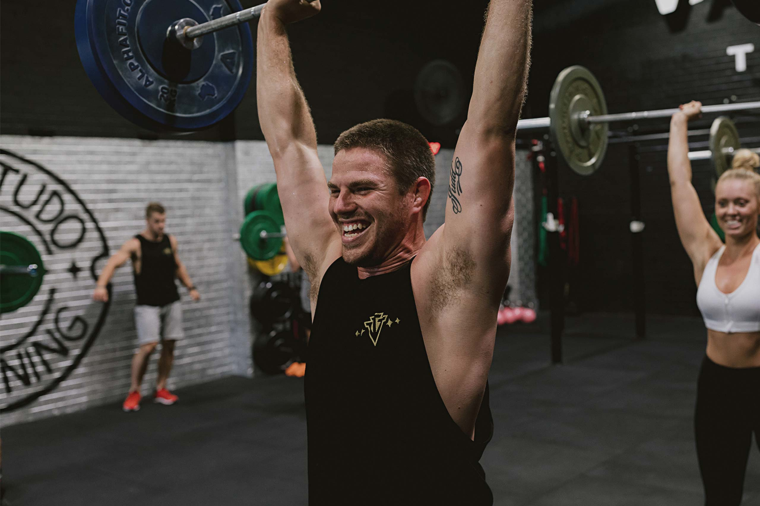 man lifting barbell weights over head