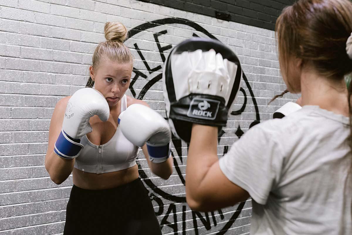 female athlete training boxing skills with coach