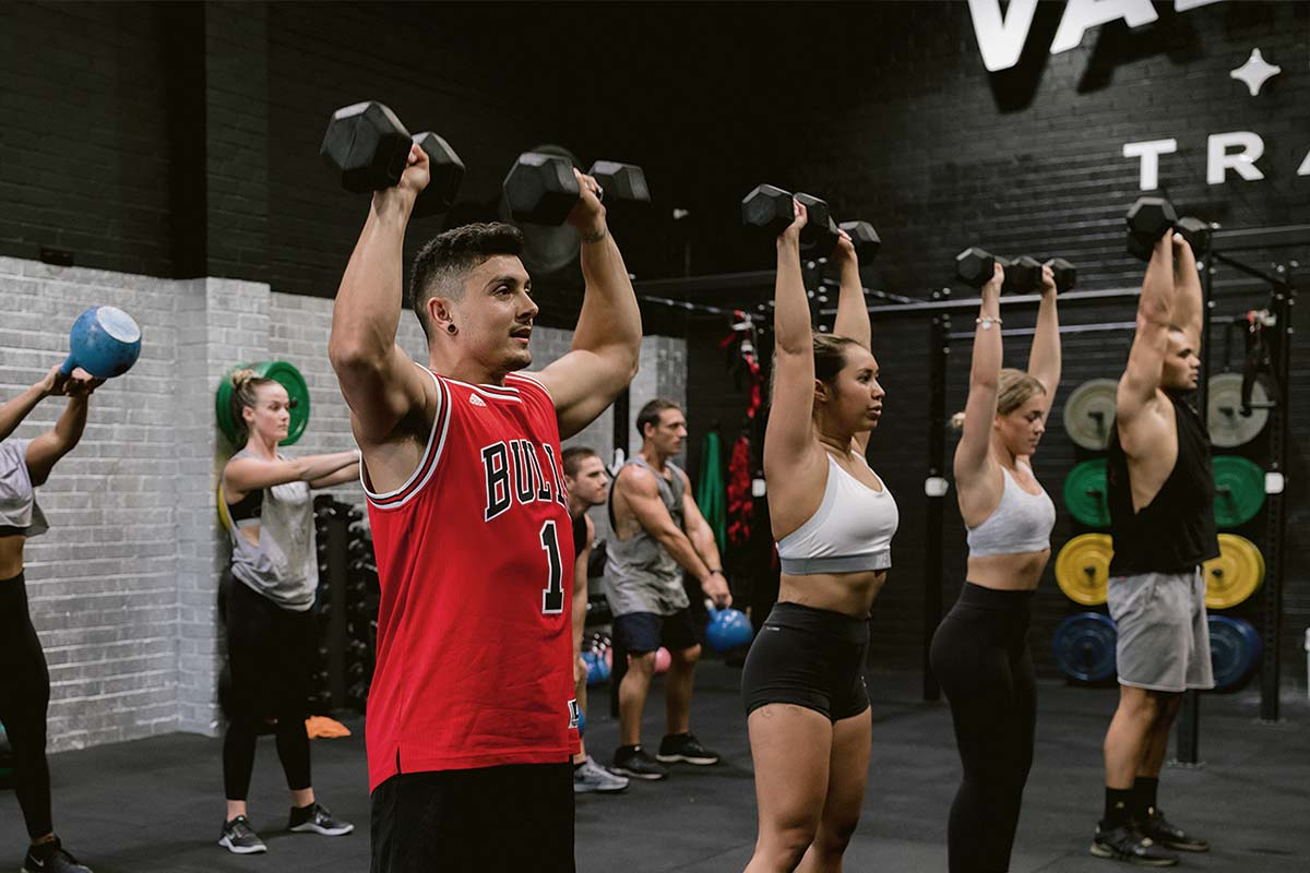 gym members lifting dumbbells above their heads