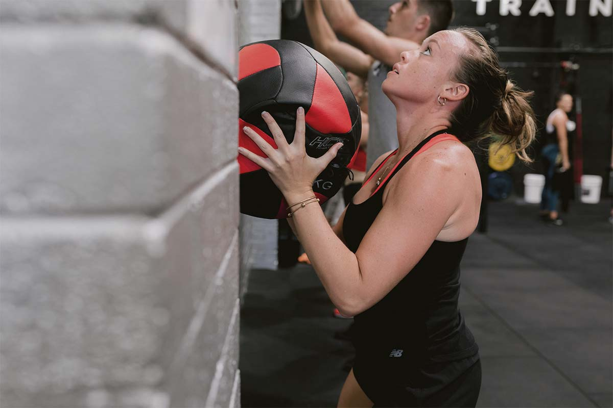 female athlete training throwing gym ball against wall