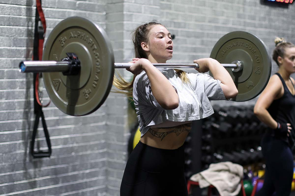 young female lifting barbell weights