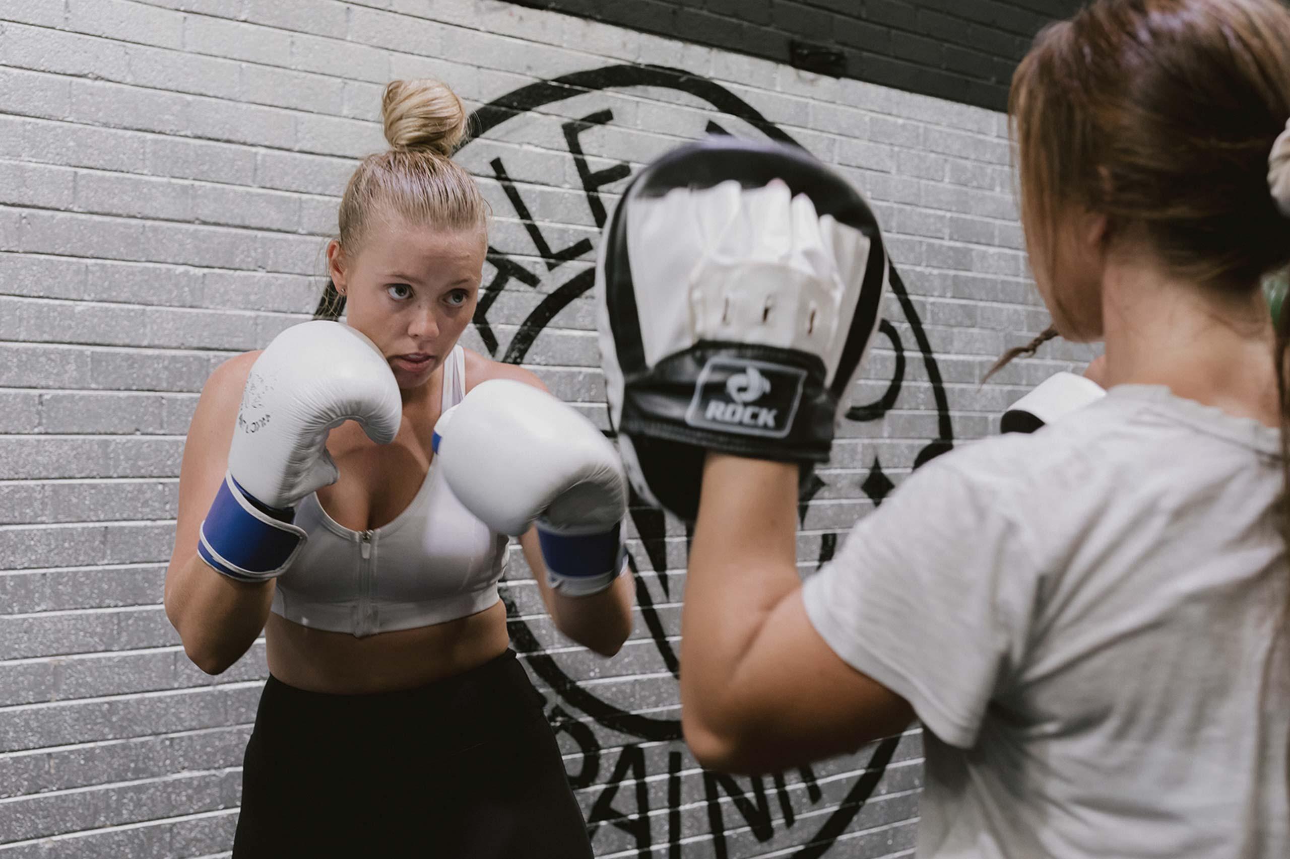 female athletes sparring in boxing training exercise