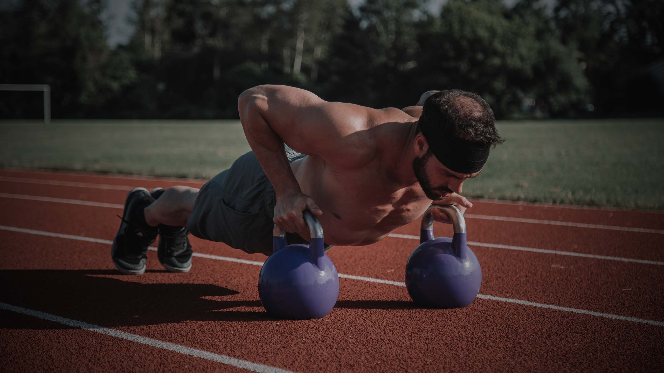 man doing pushups on sporting track field