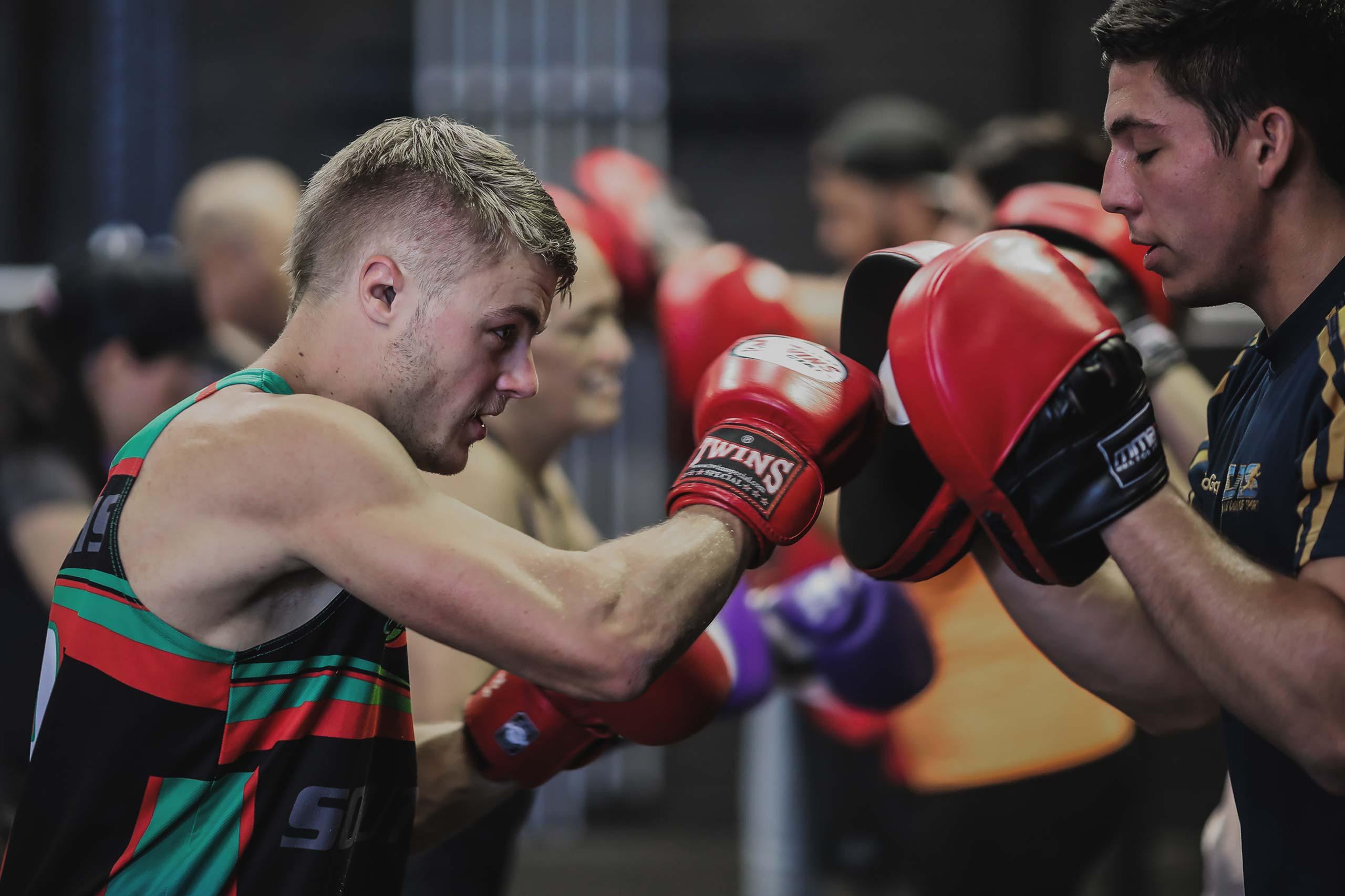 man punching boxing pads at vale tudo