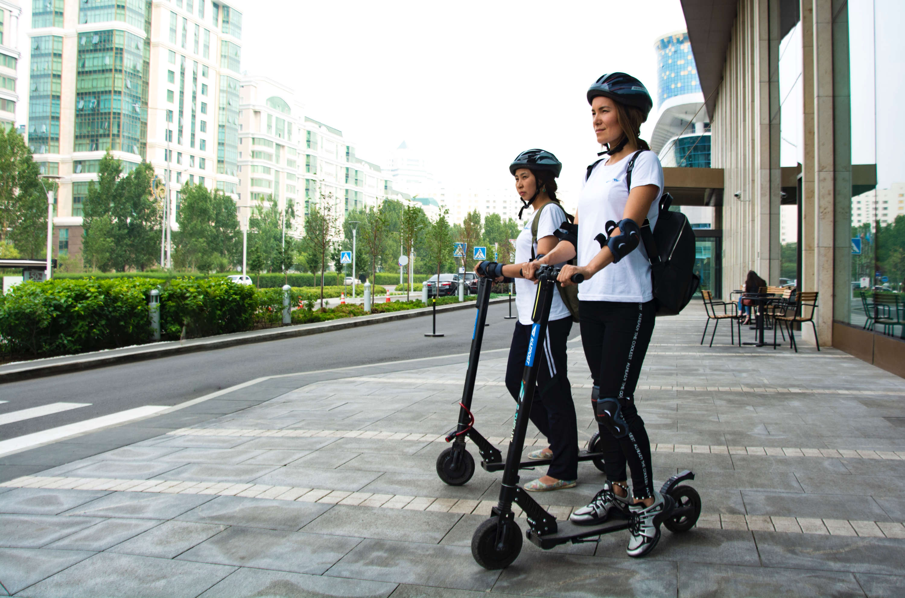 Two women standing on electric scooters in a city environment