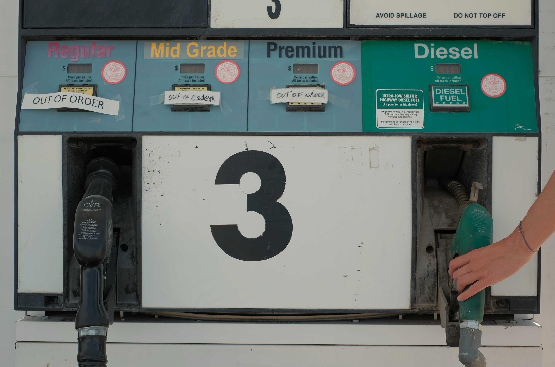 A hand reaches for a Diesel petrol pump at a gas station