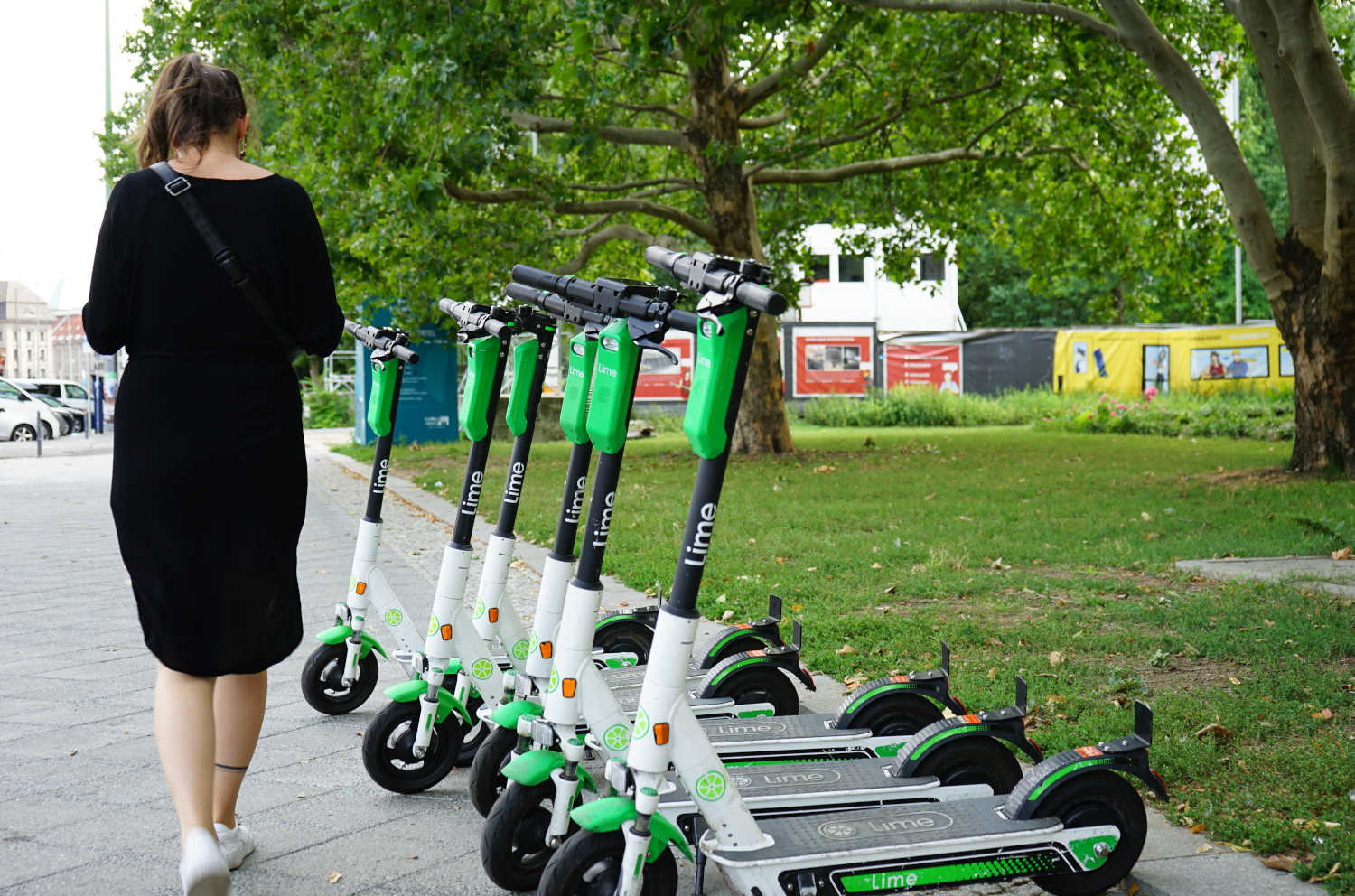 A woman walks past a fleet of dockless Lime e-scooters lined up on the pavement