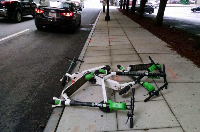 Несколько арендованных электрических скутеров Lime оставлены в куче, ограничивая доступ на тротуар.
