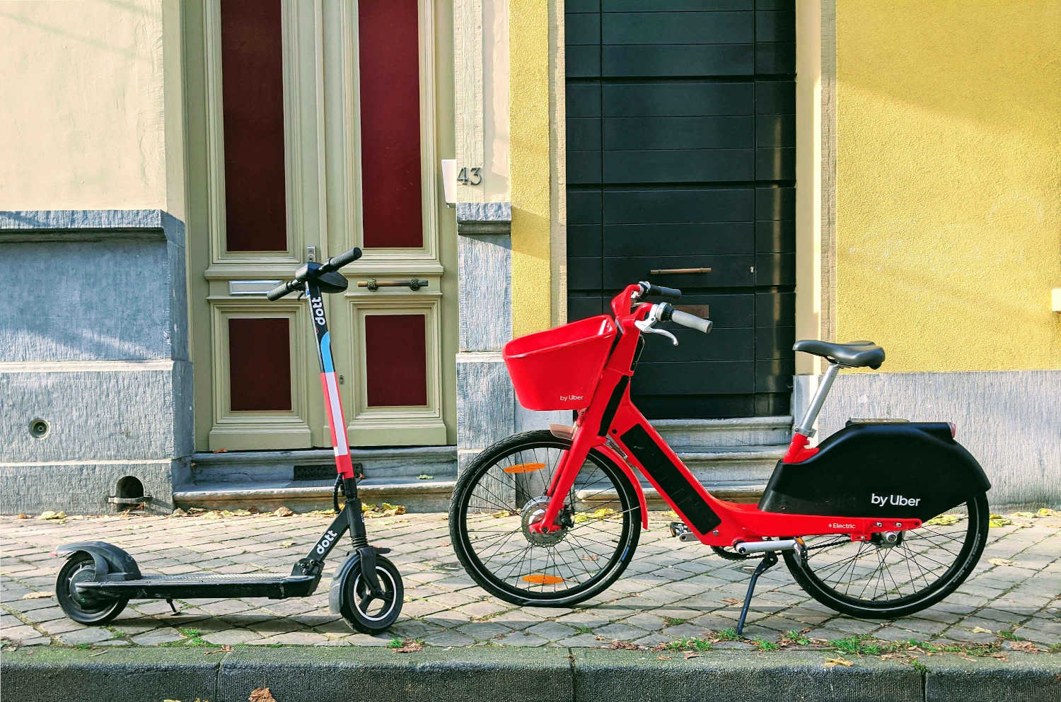 An electric scooter and an electric bike stand opposite to each other on a street.