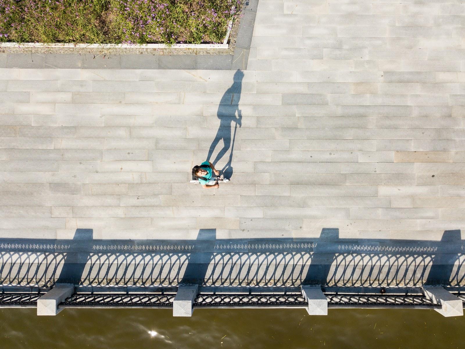 Un hombre mira a la cámara mientras conduce su scooter eléctrico sobre un puente.