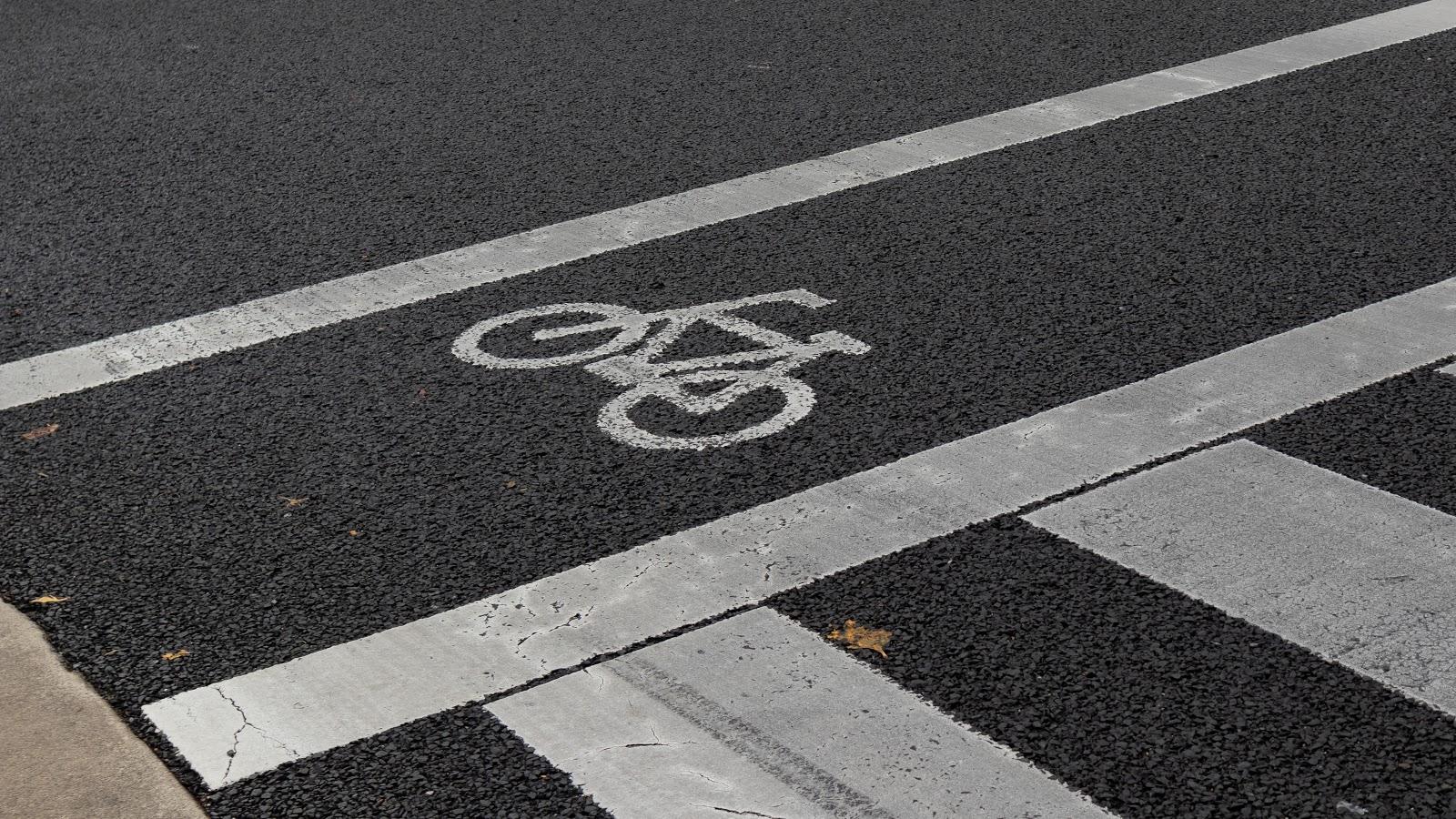 Primer plano de un símbolo de bicicleta en la carretera, que indica un carril bici.