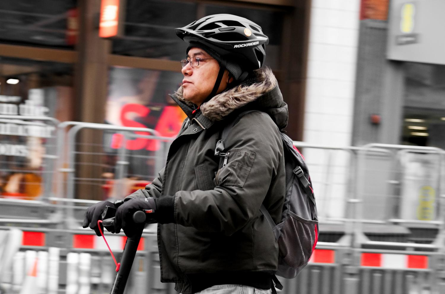 A man wearing a bike helmet rides his electric scooter through London's streets.