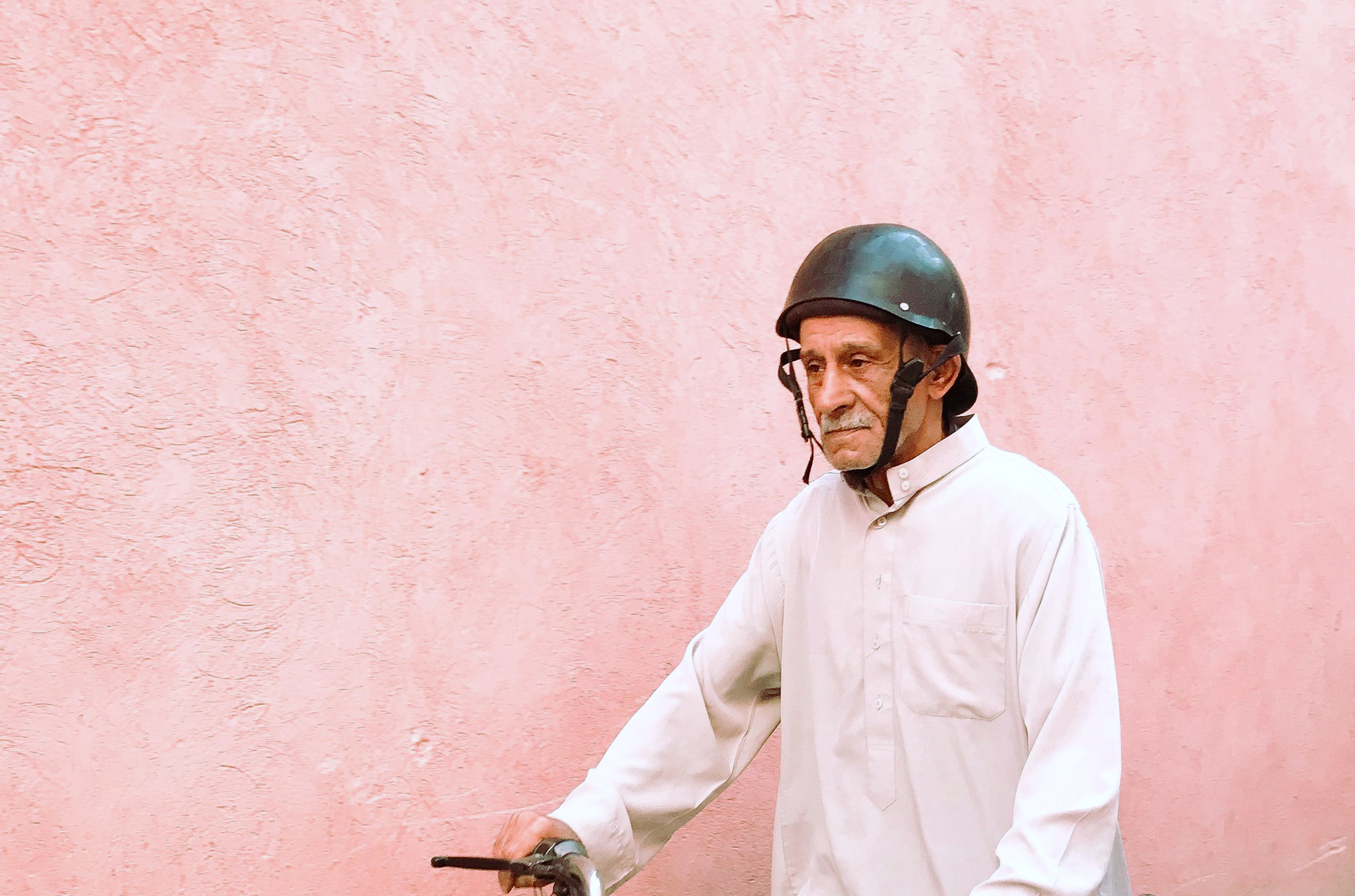 An older man dons a black rounded helmet as he rides his motorcycle near a pink wall.