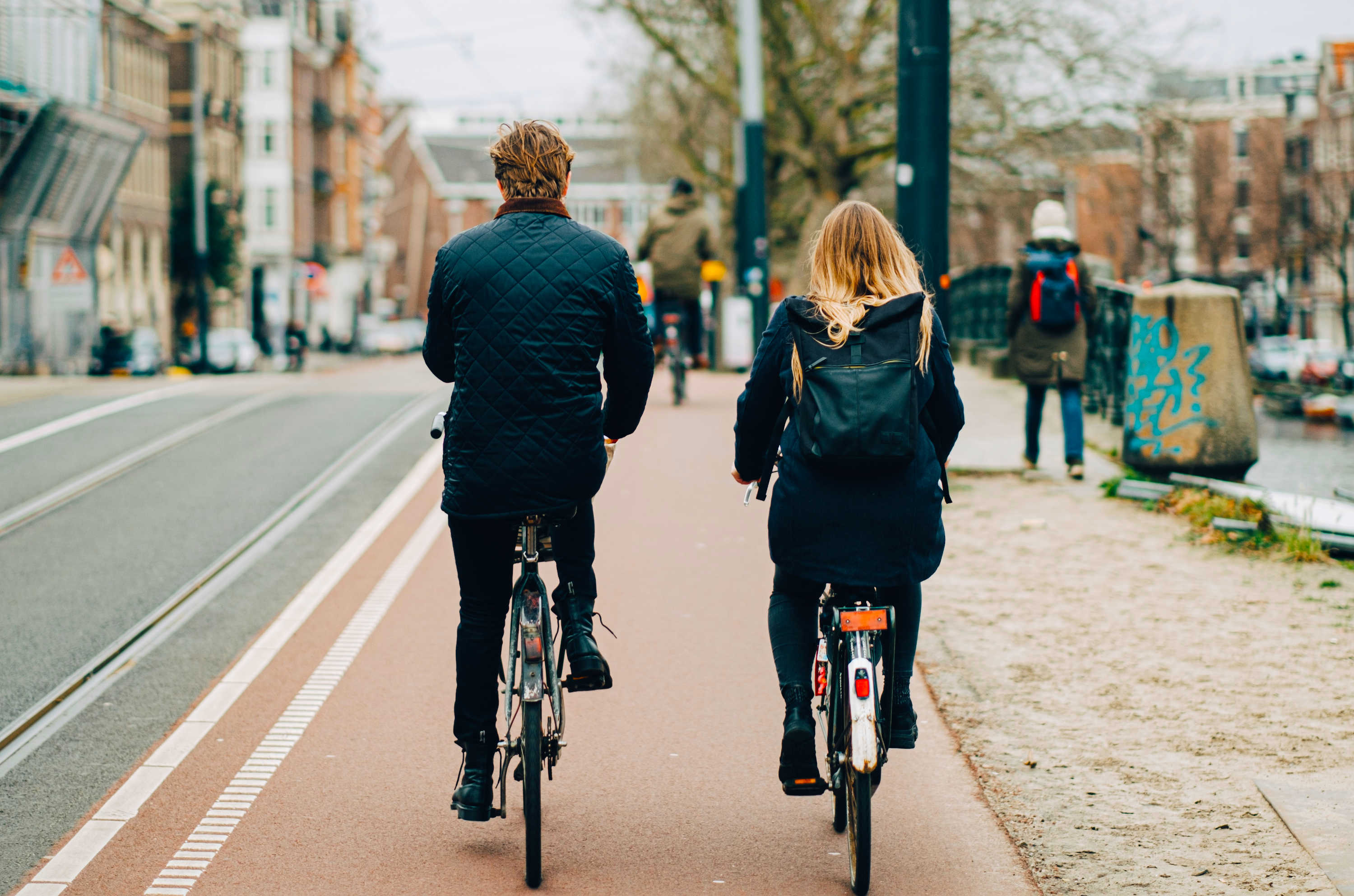 A man and woman ride their bikes along dedicated cycle lane, away from the road and pedestrians.