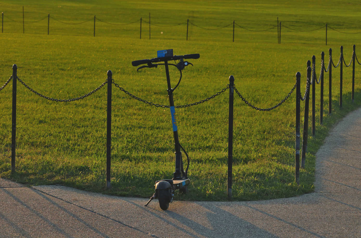 An electric scooter parked near an expanse of grass.