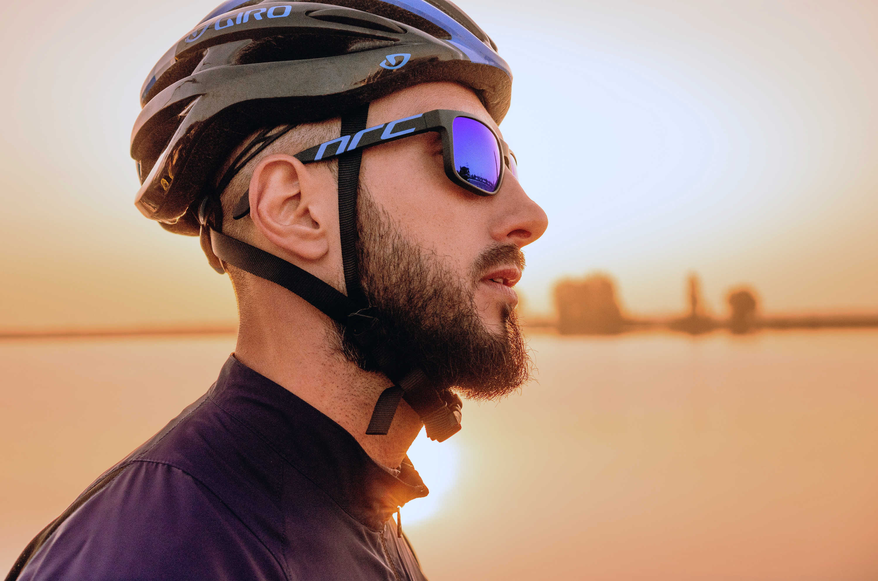 A man wears a cycling helmet and sunglasses.