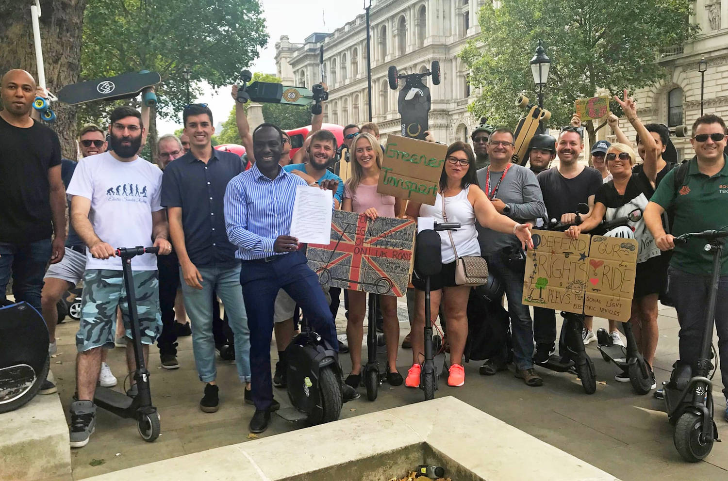 A group of smiling protesters stand proudly with their electric scooters, skateboards, and unicycles outside Downing Street.