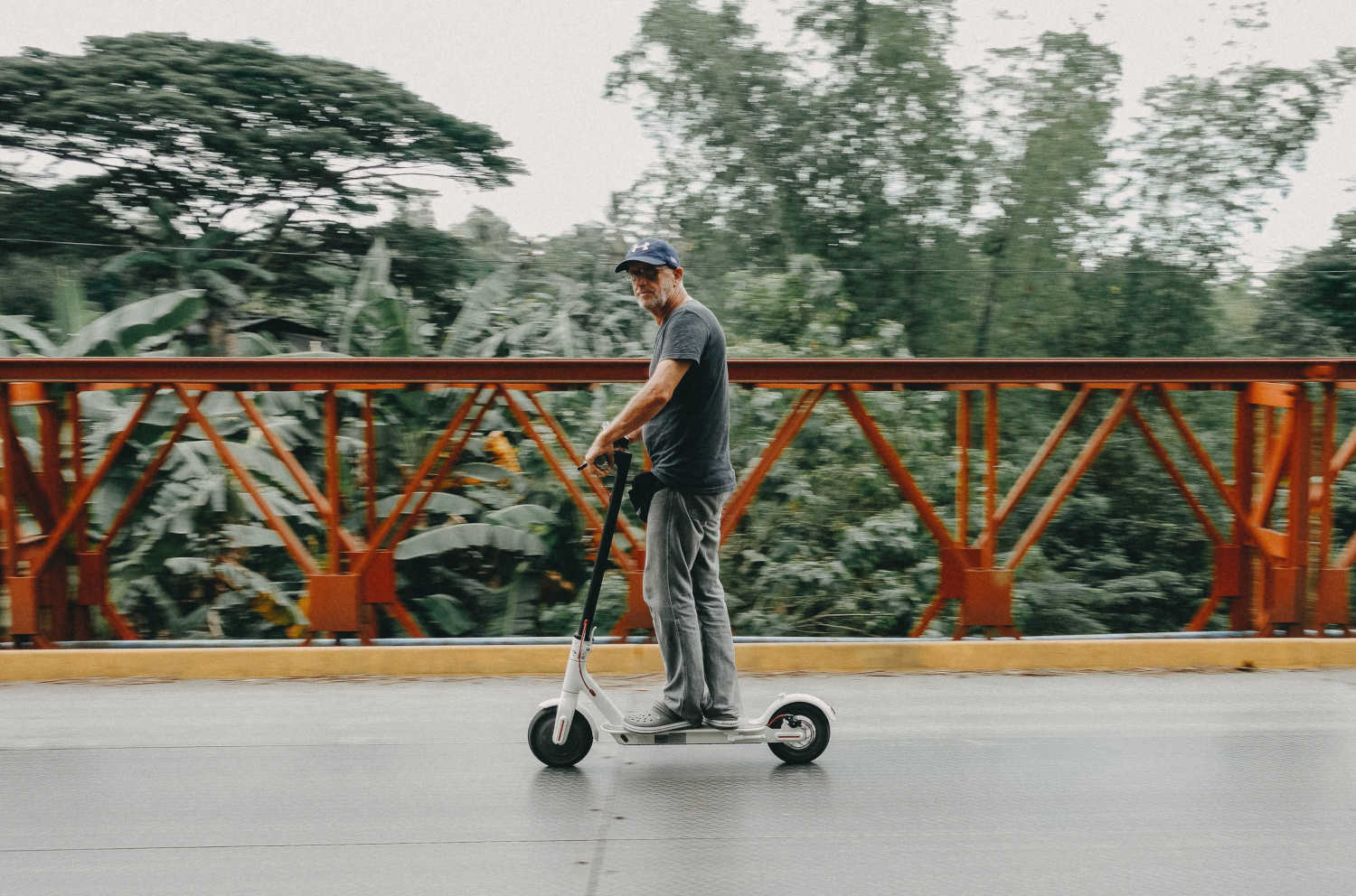 A man rides his electric scooter on a bridge.
