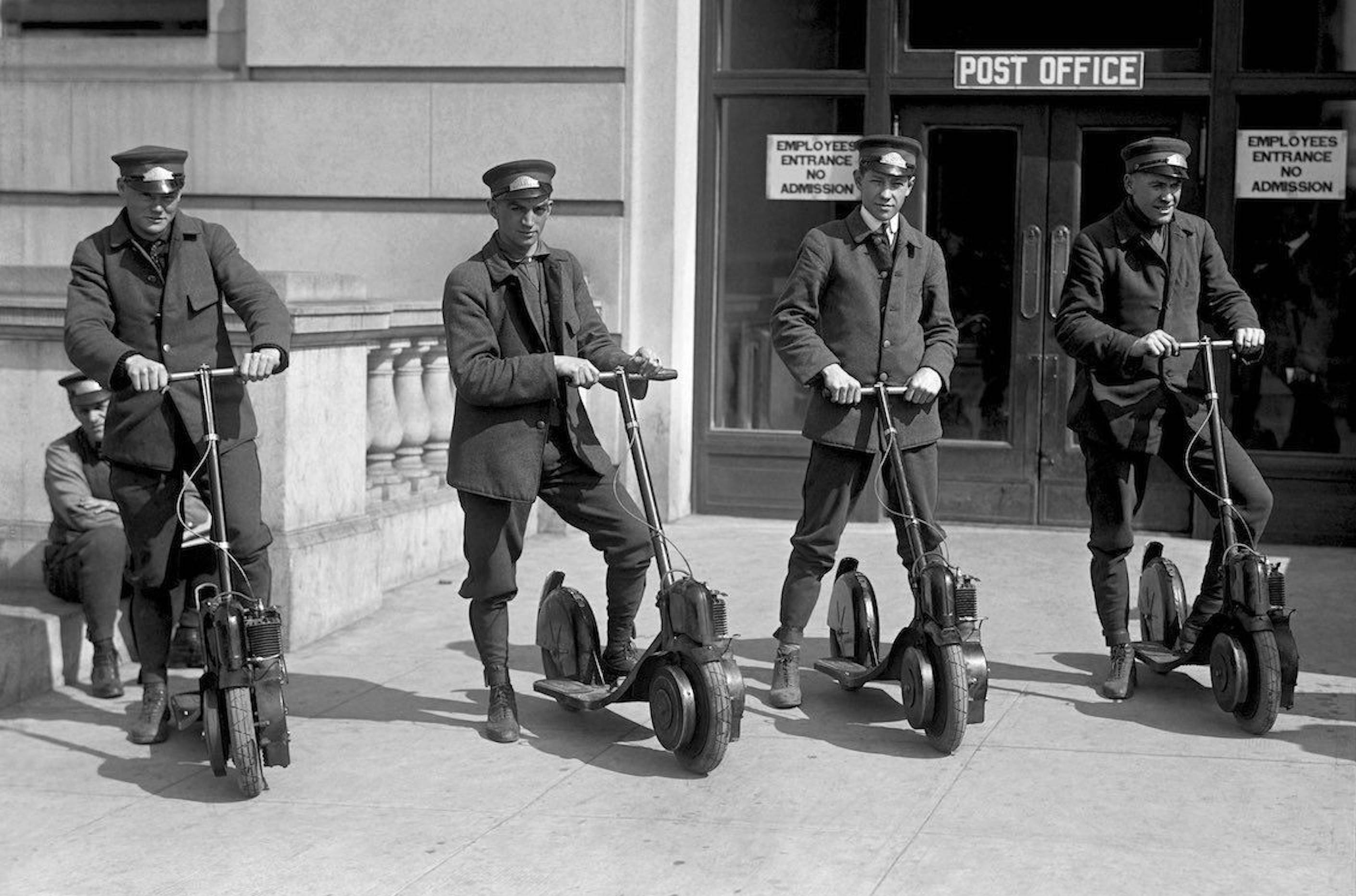 Four 20th Century postmen stand on their Autopeds, the electric scooters of their time.
