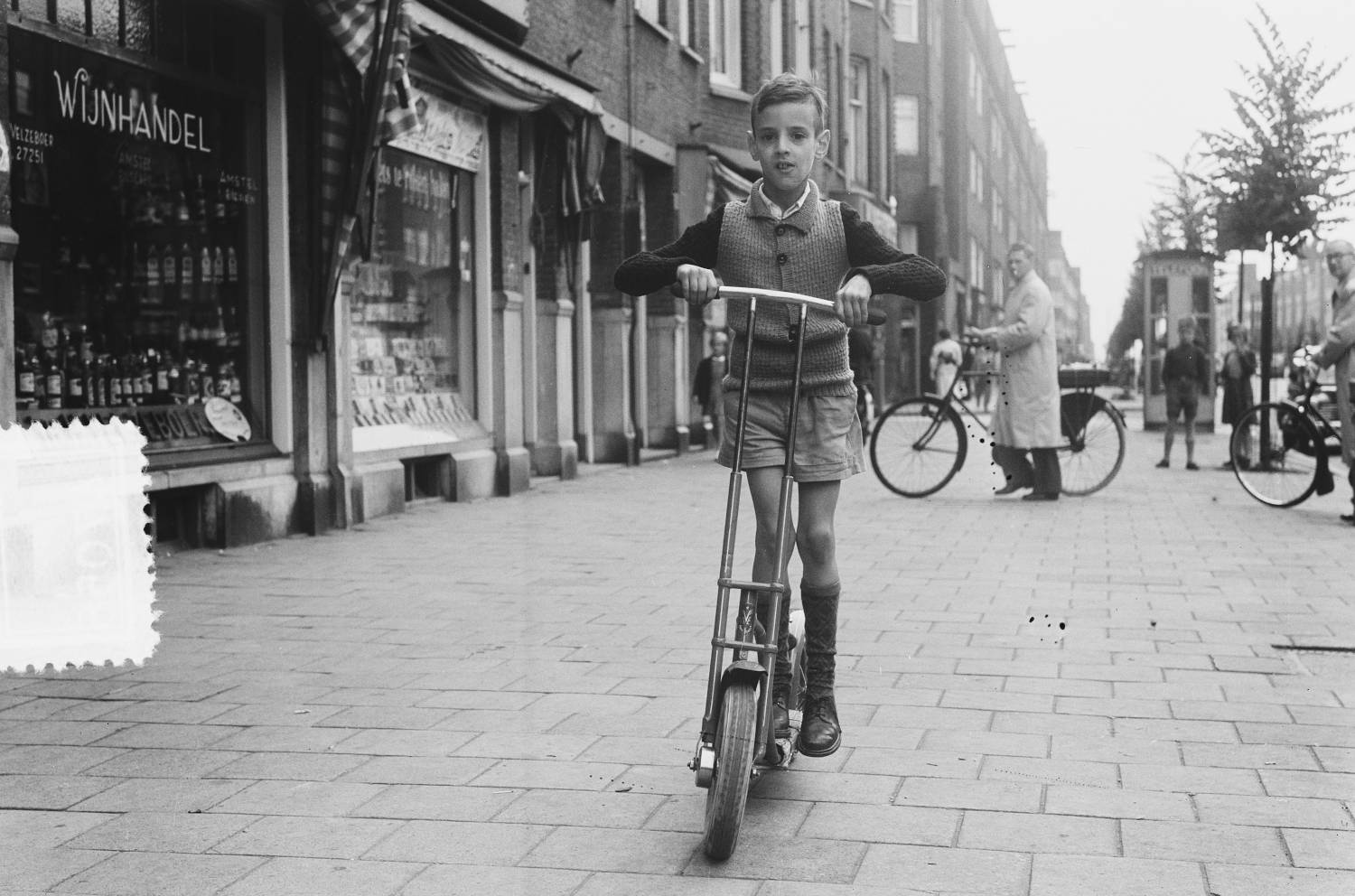 A young boy rides his Autoped through the streets of Amsterdam.
