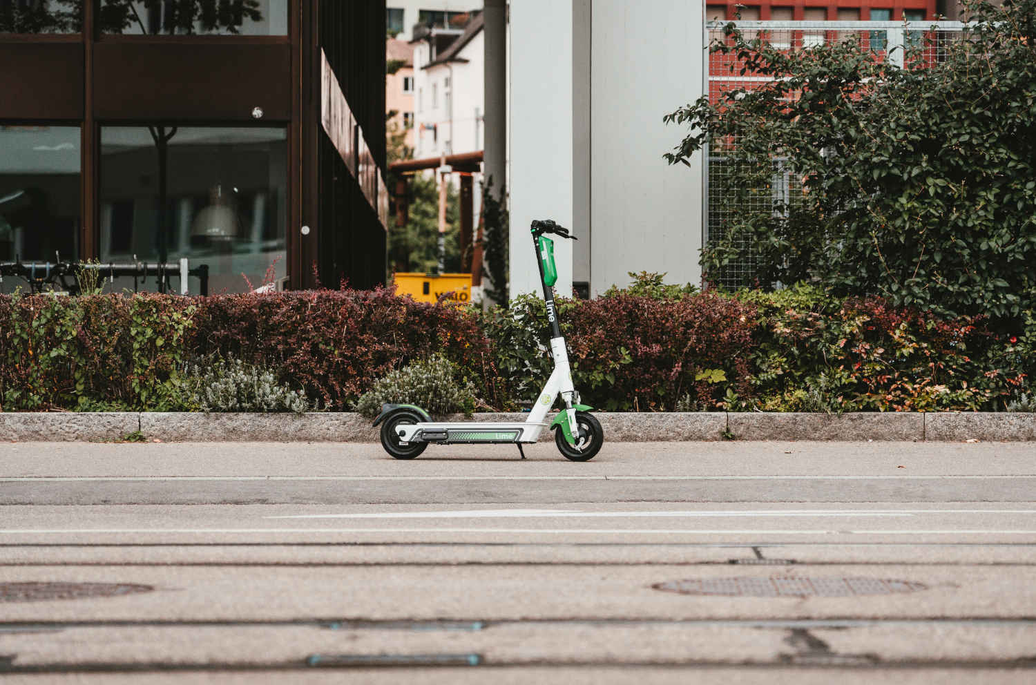A Lime rental e-scooter stands alone on a city street.