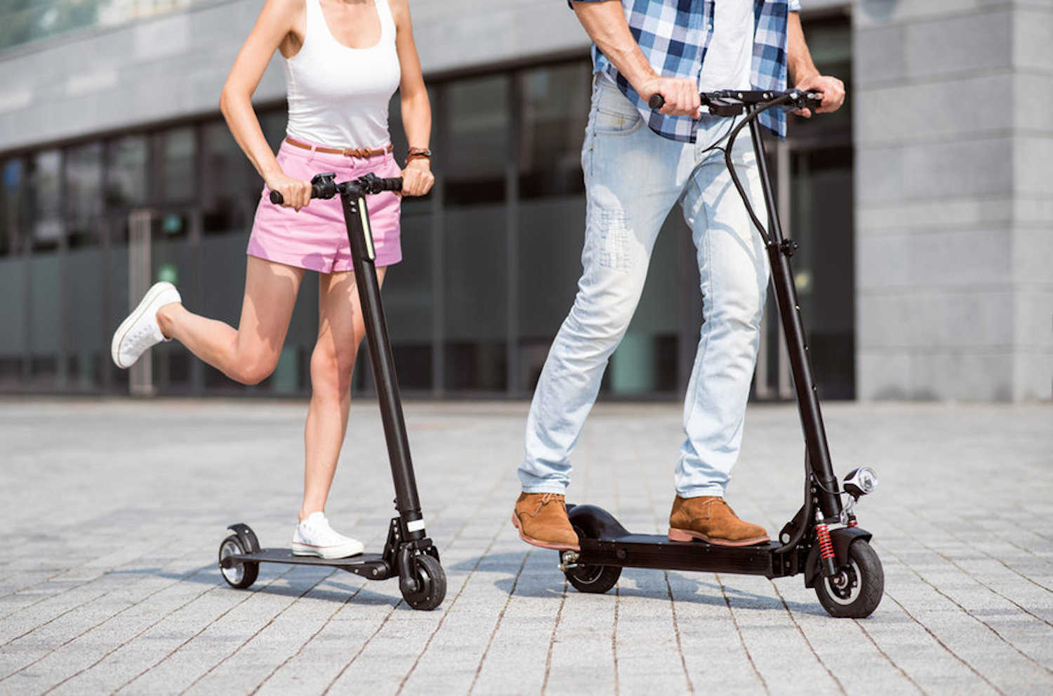 A man and a woman ride electric scooters on a pavement