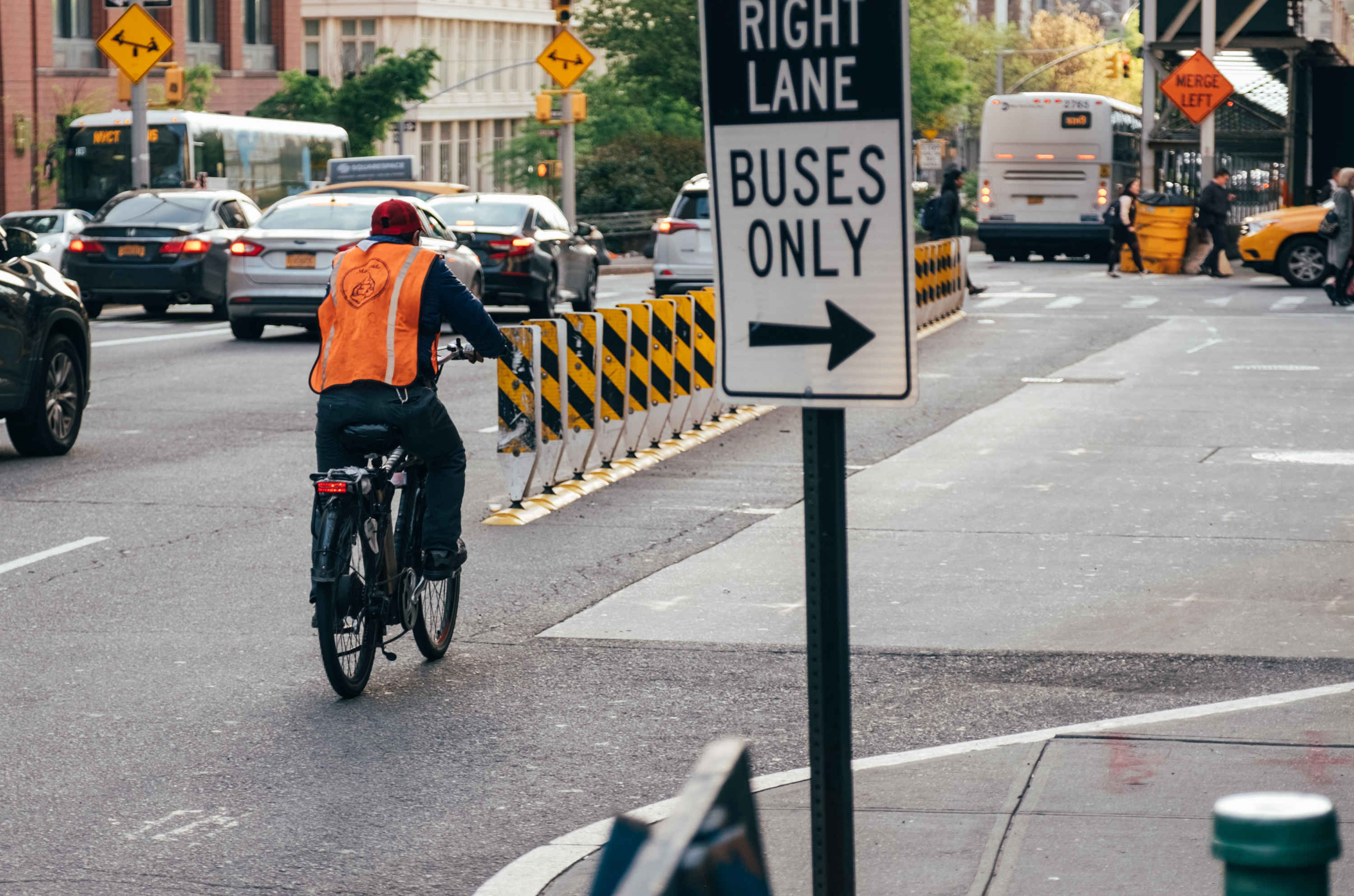 A cyclist rides down a pop-up cycle lane, protected by temporary barriers.