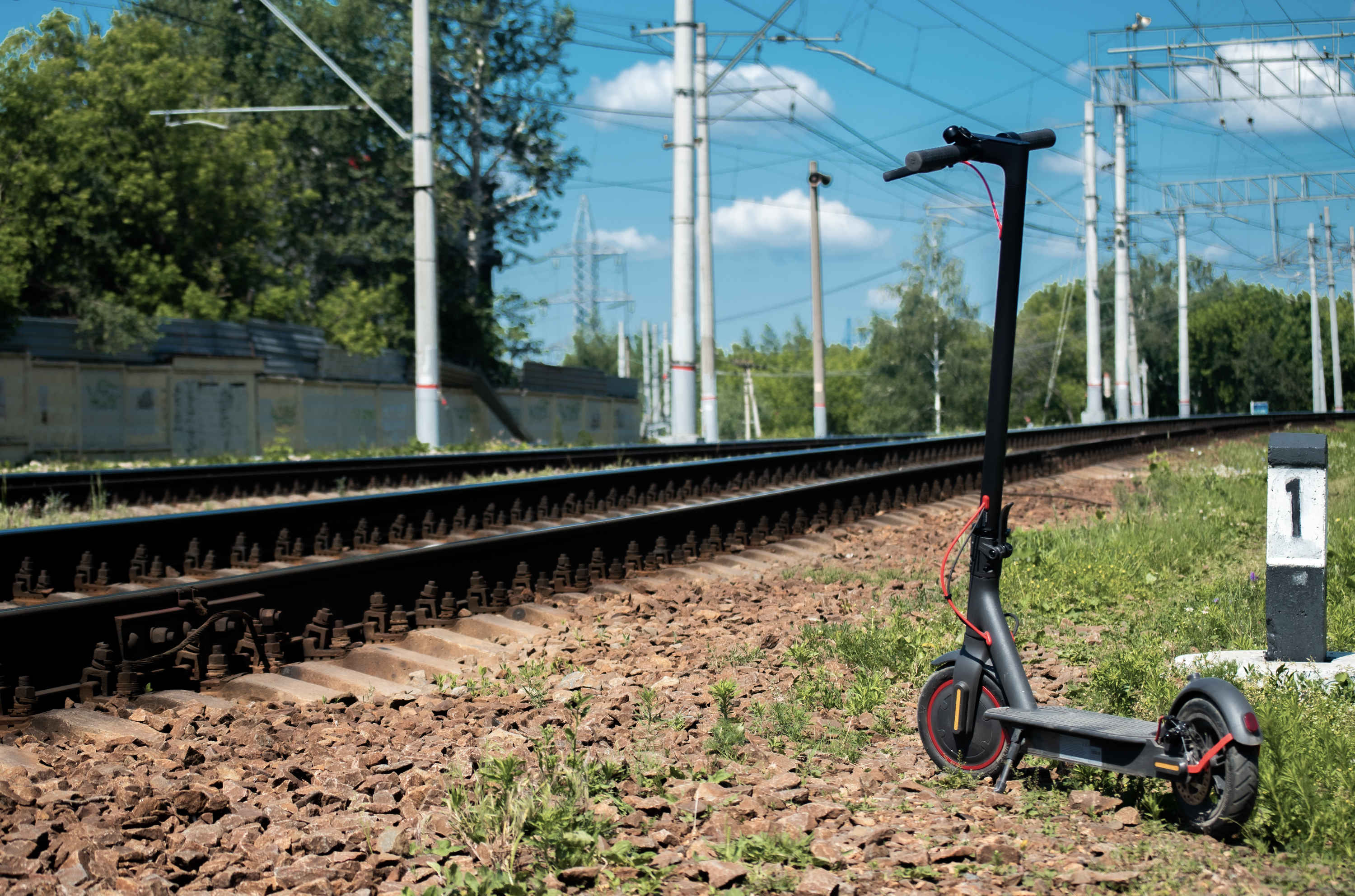 An electric scooter stands parked by a railway line.