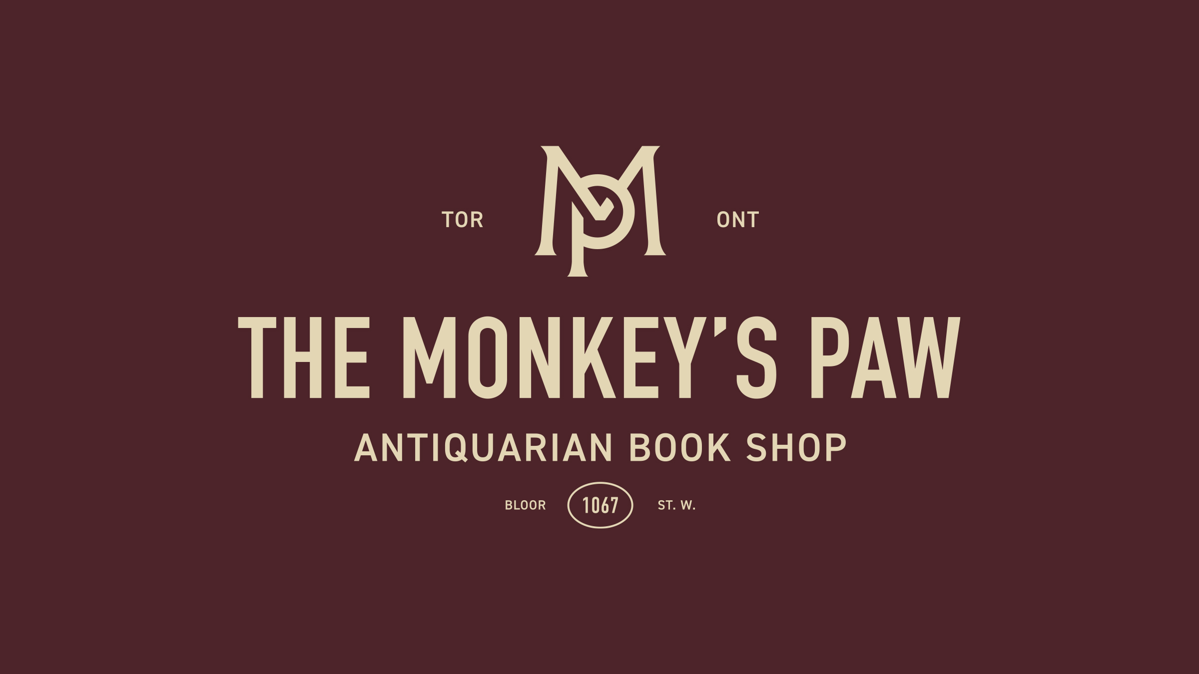 The Monkey's Paw brand logo cream on maroon