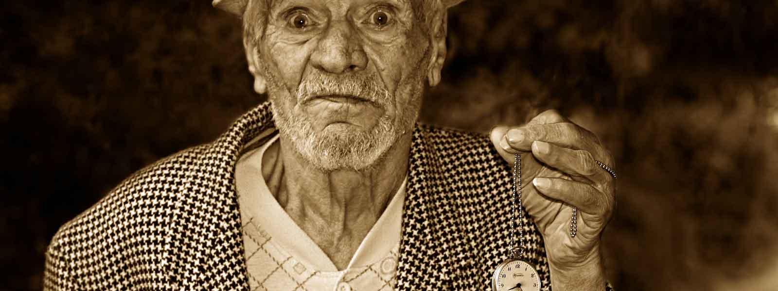 oude man met een zakhorloge in zijn hand